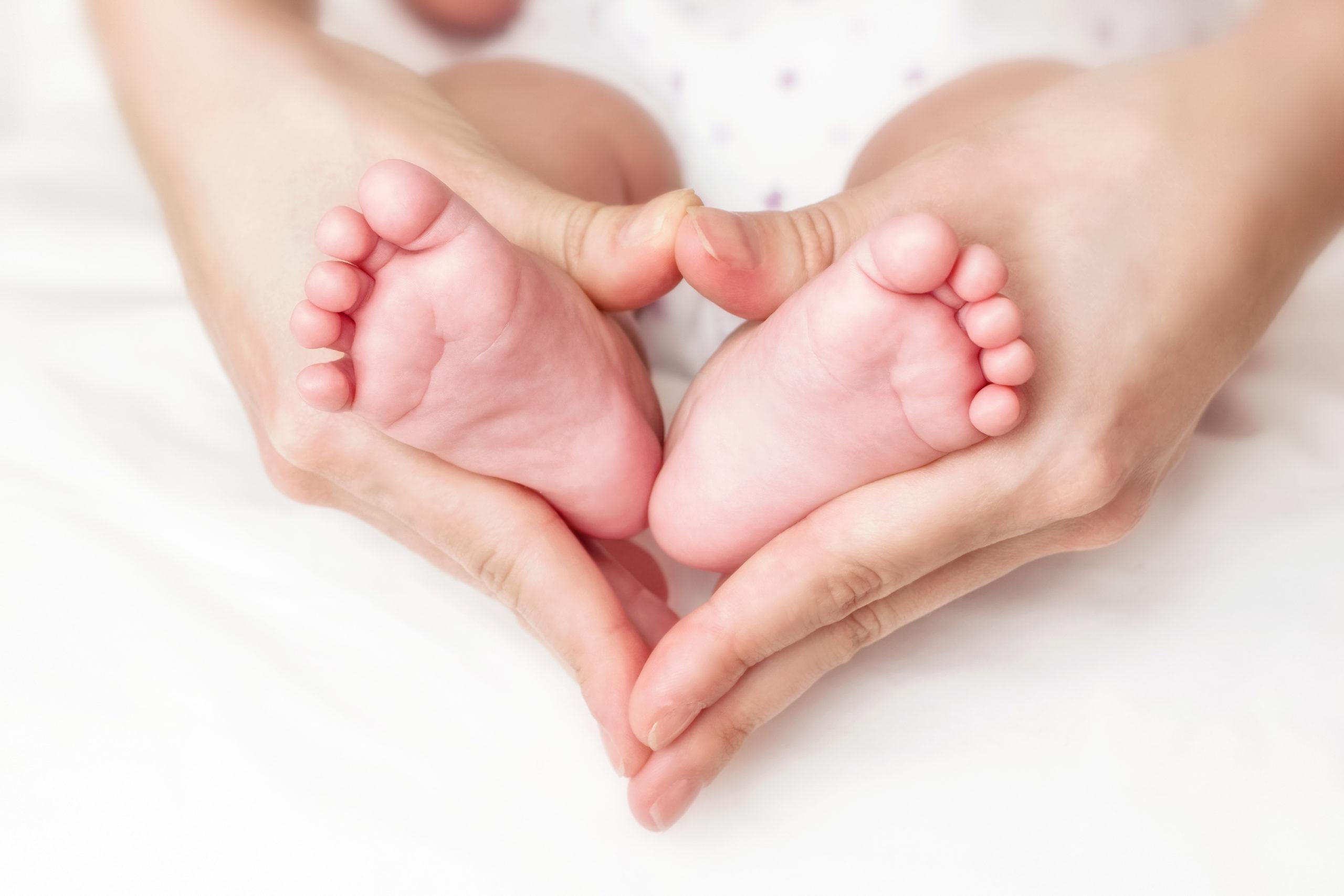 Zoneterapi til baby. Kvindehænder og babyfødder.